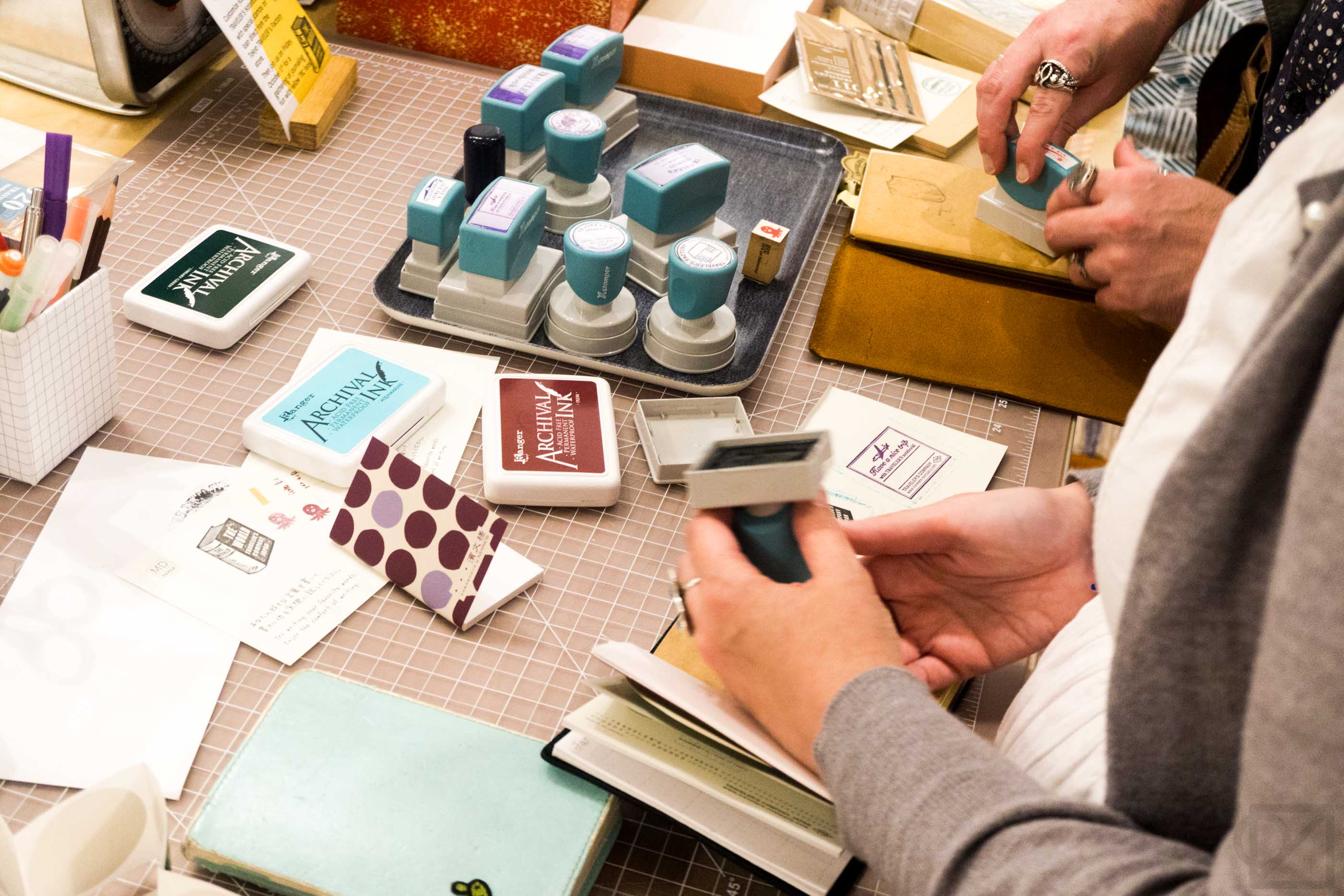 A busy atmosphere builds around the stamp table.