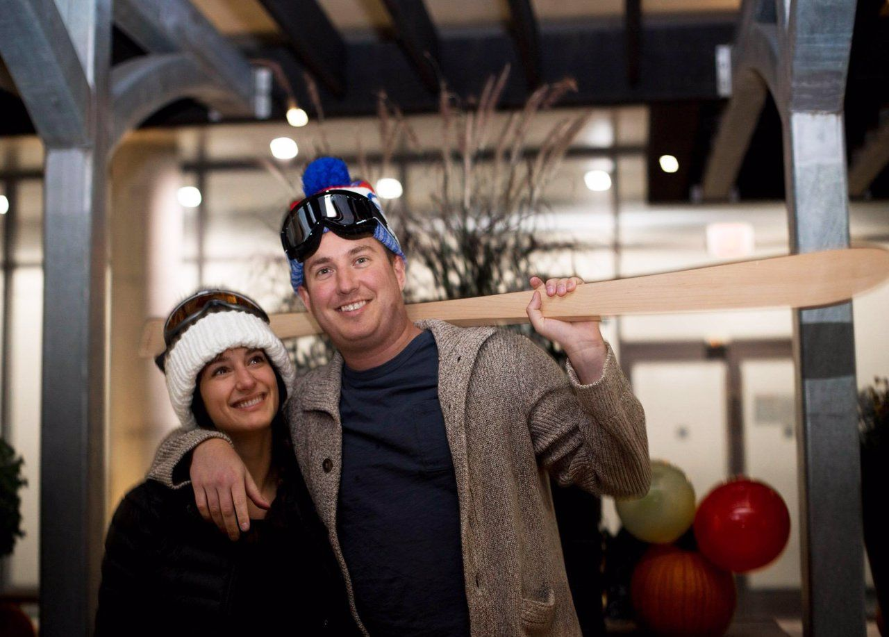 Smiling couple dressed up in Ski clothes at a party. The man is holding a maple Shot Ski over his shoulder.