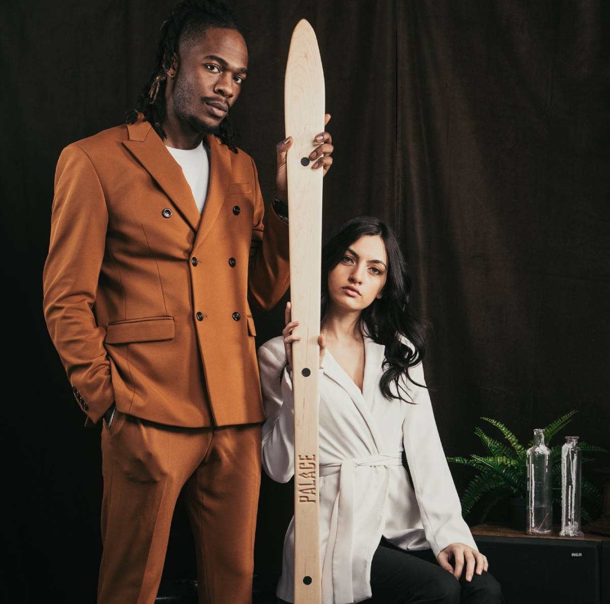A suited man and seated woman posing with a Palace Shot Ski