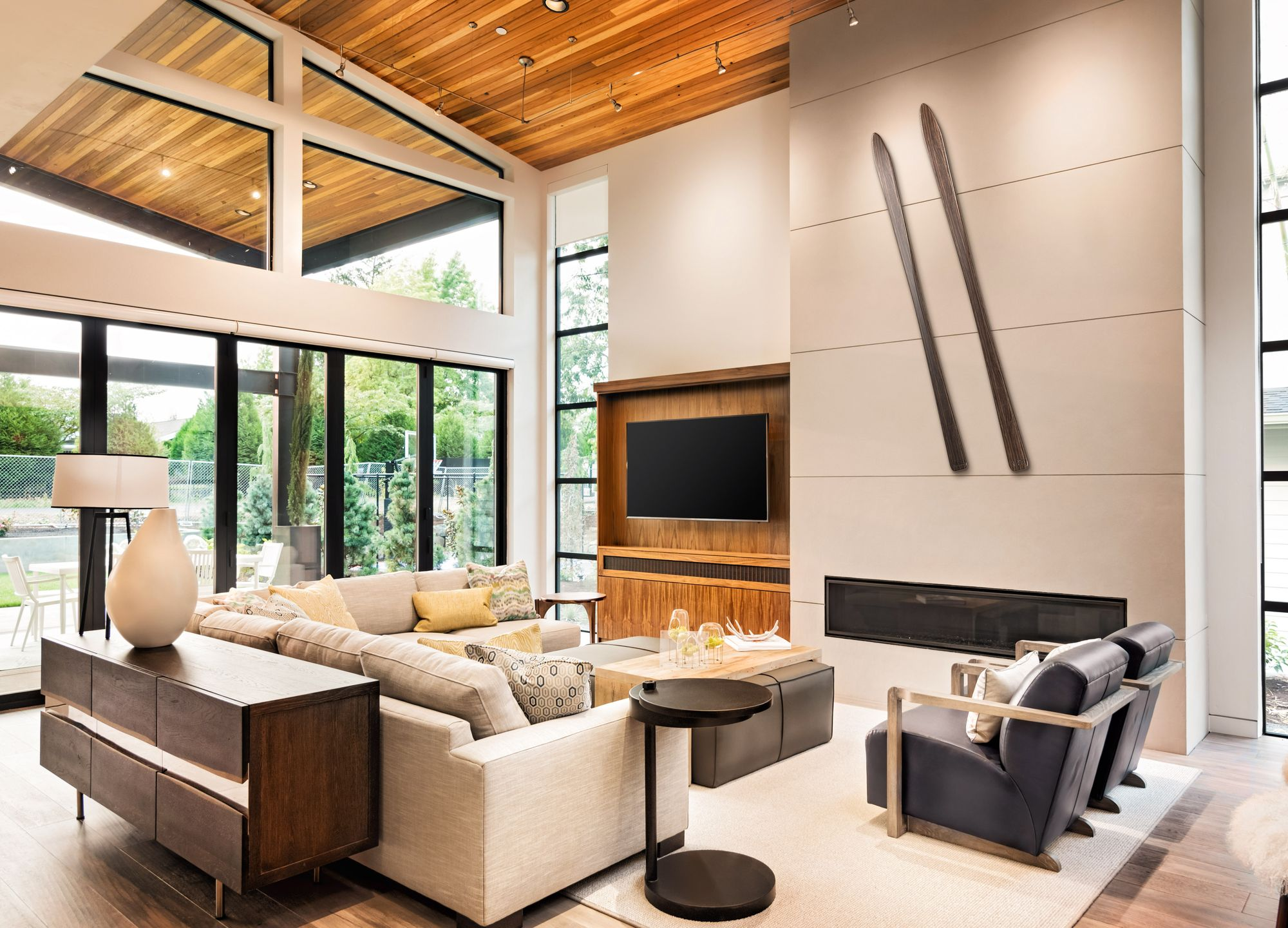 A beautiful modern living room with two walnut Shot Skis hung diagonally above the fireplace