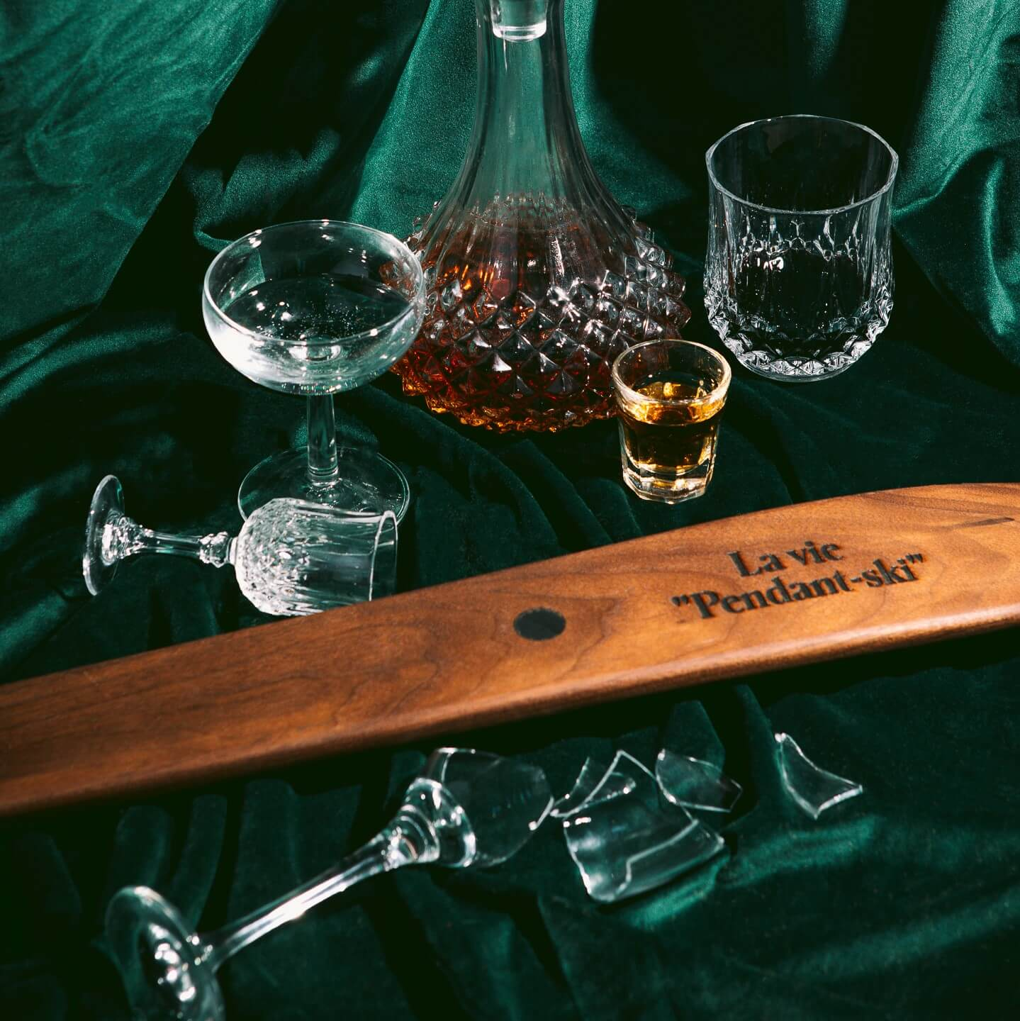 Flatlay of engraved walnut shot ski surrounded by messy drink glasses on a green curtain.