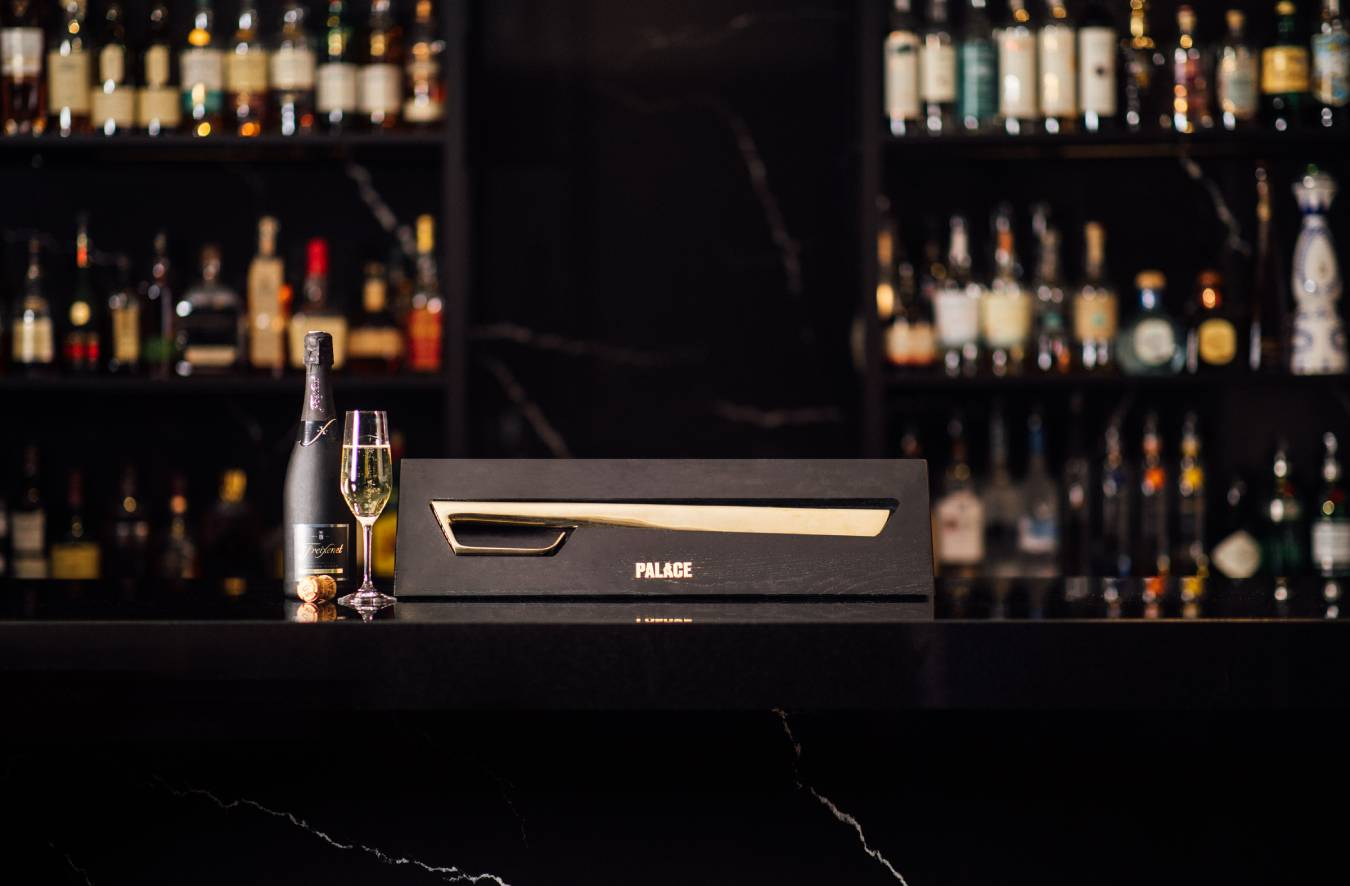 The Champagne Sabre beautifully displays itself in front of a cellar full of bubbly champagne.