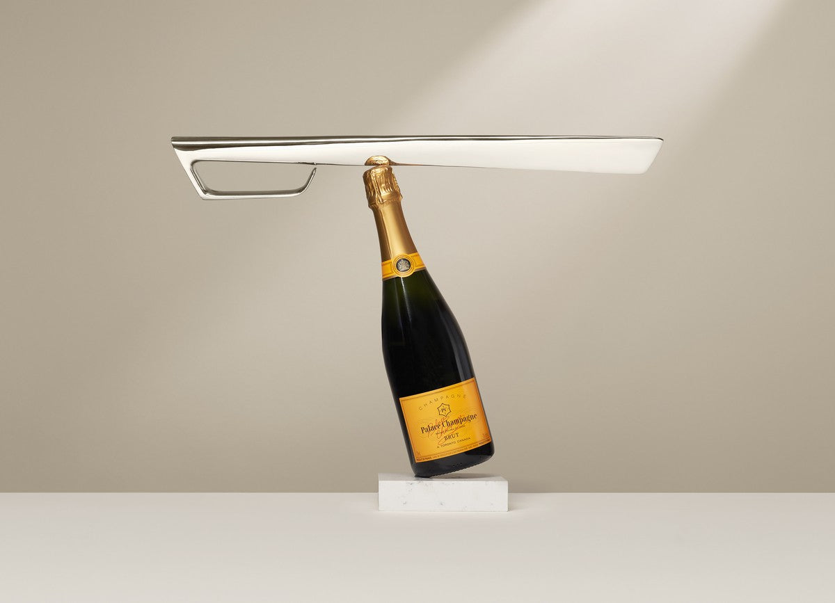 Silver champagne sabre balanced horizontally on a leaning champagne bottle.