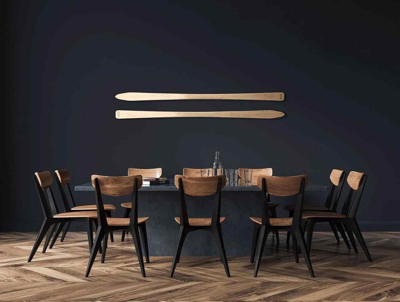 A beautiful dining room table with chairs around it on wood floor. Above the table are two Maple Shot Skis hung horizontally on the wall