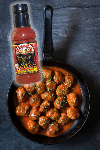 Claude's Hot & Spicy Sauce poured into a cast iron pan with meatballs