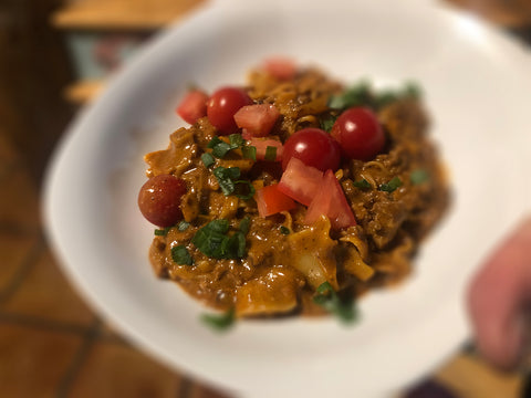 A bowl of cooked Casa Corona Enchilada Pasta with green onion and tomato garnish