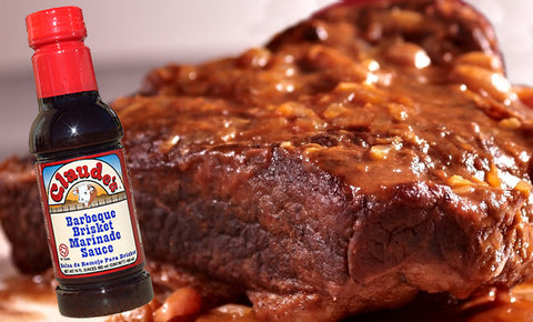 Claude's Sauces 16 oz. bottle of BBQ Brisket Marinade with a sweet and sour brisket in the background.