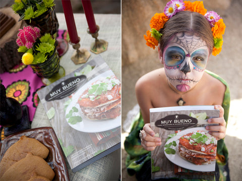 A Day of the Dead painted girl holds a Muy Bueno Cookbook