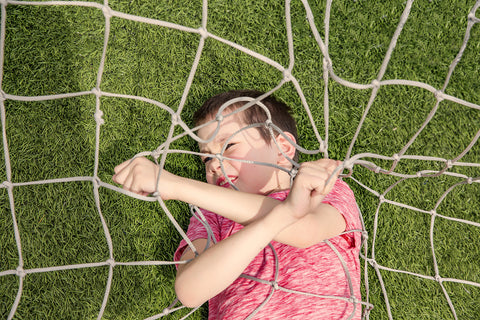 Boy stuck in soccer netting
