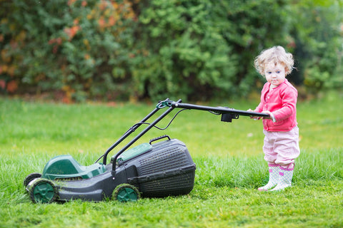 Toddler pushes lawnmower