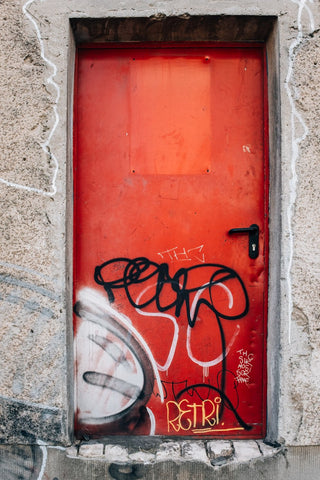 big-red-graffitied-door-in-concrete-wall