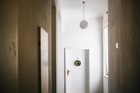 white-hallway-with-a-white-door-and-green-wreath Interior Doors Designed
