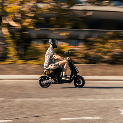 Man riding Bilis Electric Moped going fast