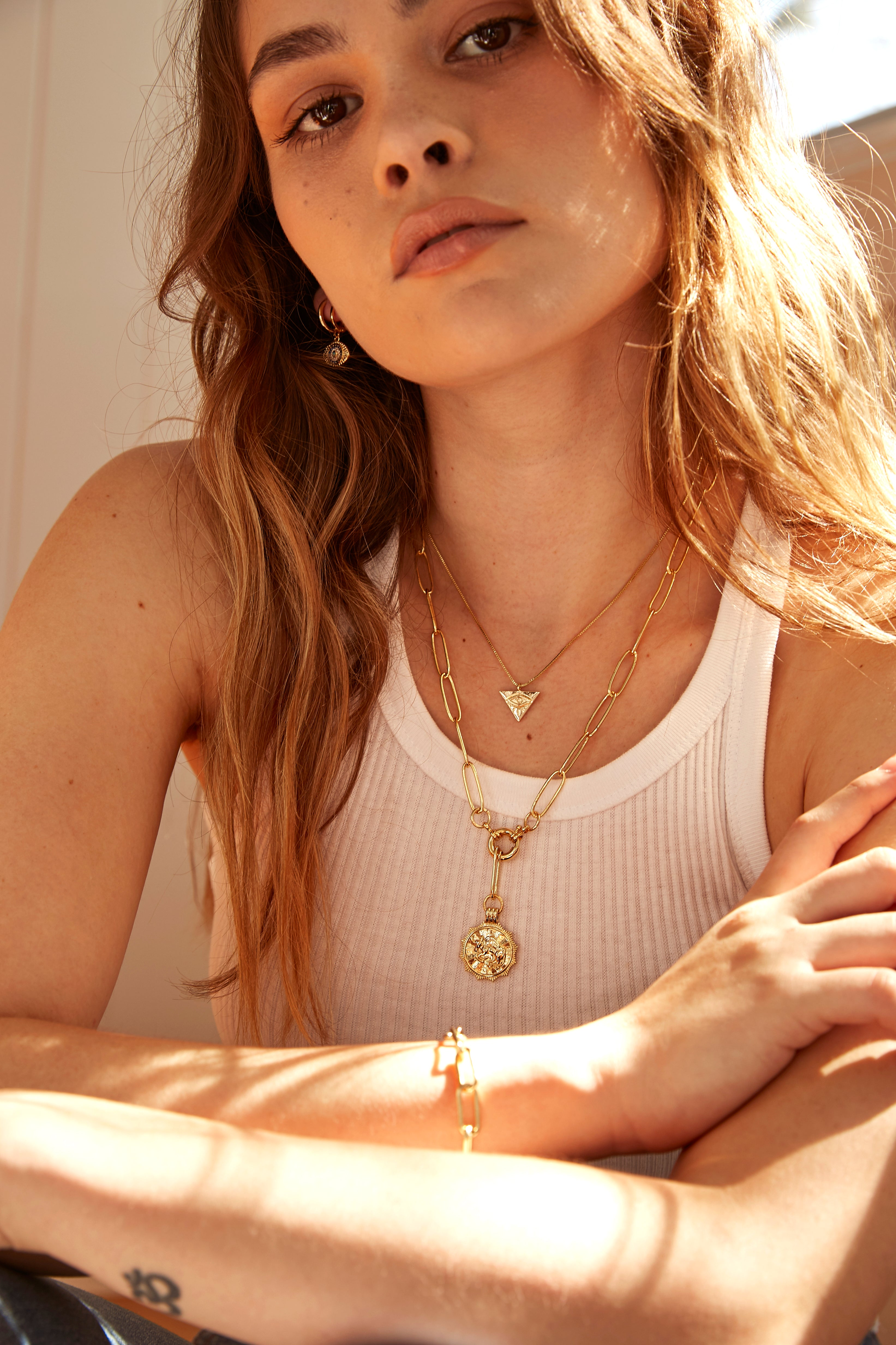 Model wearing AW Boutique's gold filled 18 inch paperclip oval link chain necklace with a front clasp. This chain features a zodiac pendant in the sign of your choice. Taurus is shown. Also shown is our Eye of Providence Chain and Evil Eye Huggie earring.