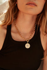 Load image into Gallery viewer, Model wearing AW Boutique's gold filled 16 inch textured rolo chain (6mm link diameter) with an Evil Eye Medallion pendant featuring clear and blue cubic zirconia crystal detail.