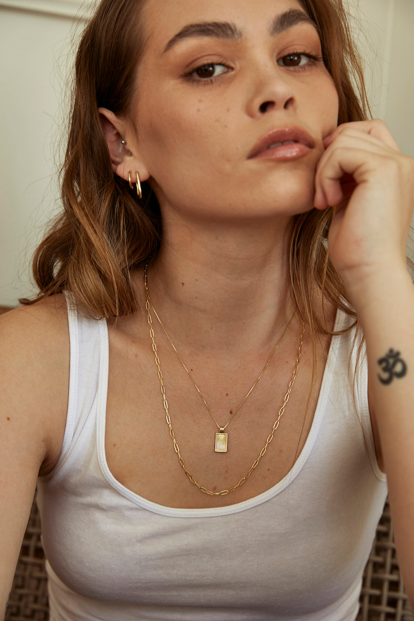 Model wearing AW Boutique's 14mm diameter Everyday Sleeper earrings alongside the Rectangle Hoop, the Sunburst Tag Pendant Chain and the Paperclip Layering Chain.