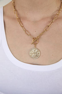 Model wearing AW Boutique's gold filled 18 inch bold paper click oval chain necklace with a front toggle clasp and lucky coin medallion featuring 7 lucky symbols.