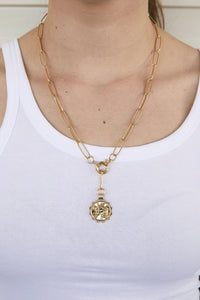 Model wearing AW Boutique's gold filled 18 inch paperclip oval link chain necklace with a front clasp. This chain features a zodiac pendant in the sign of your choice. Taurus is shown.