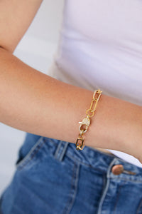 Model wearing AW Boutique's gold filled bracelet in a large paperclip link and finished with a cubic zirconia crystal filled lobster clasp closure.
