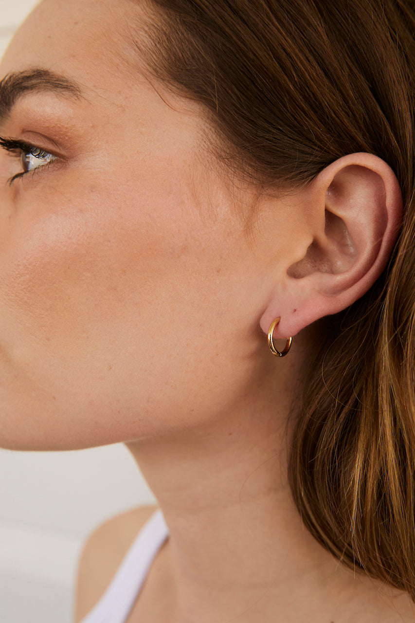 Model wearing AW Boutique's 14mm diameter Everyday Sleeper earrings.