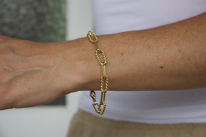 Model wearing AW Boutique's Twisted Oval Link Bracelet.  This is a beautiful, textured piece that is both bold and feminine. The twisted links bring a softer edge to this striking link. You can wear this gold treasure alone or layer with finer bracelets to give it an edgier look. Whatever way you choose to wear this bracelet it will quickly become a staple.