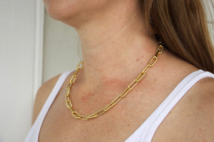 Model wearing AW Boutique's Twisted Oval Link Chain.  This is a beautiful, textured chain that is both bold and feminine. The twisted links bring a softer edge to this striking piece. Sitting at 19 inches long you can wear this gold treasure alone or layer with a finer chain to give it an edgier look. Whatever way you choose to wear this piece it will quickly become a staple.