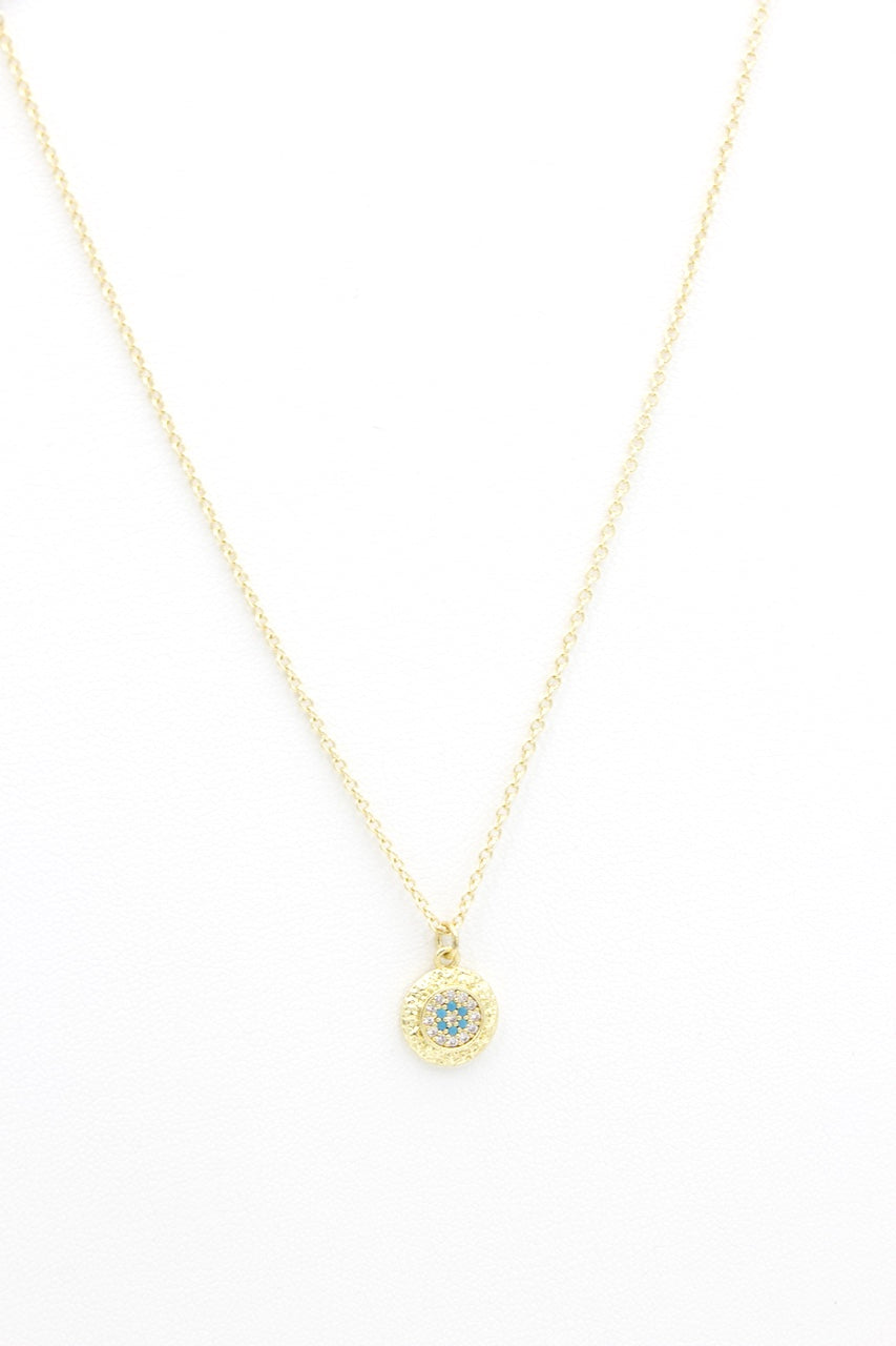 AW Boutique's the Mini Evil Eye chain is a dainty piece that will protect you against the evil eye gaze and negative energies. Wear it for protection and to bring you good luck. The fine chain sits at 16 inches and compliments the charm that has a hammered effect around the outside, capturing the light from all angles. The inner centre of the charm is finished with clear white cubic zirconia and turquoise coloured stones to form the eye.