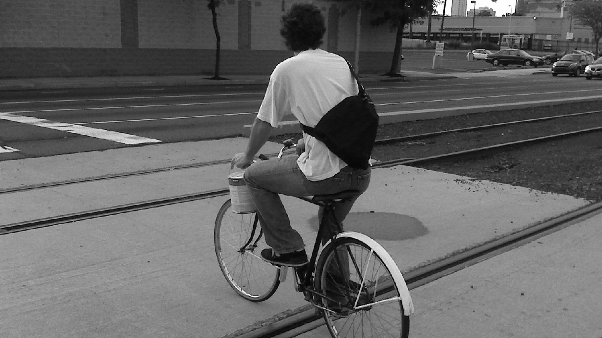 Jaime rides bicycle across train tracks.