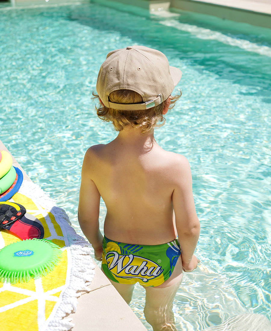 Young boy in pool wearing Wahu x Budgy Smuggler next to Wahu Soak N' Throw and Wahu Aqua Glider