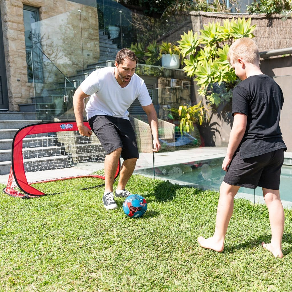 Father and Son in the backyard playing with the Wahu Pop Up Soccer Goals Set