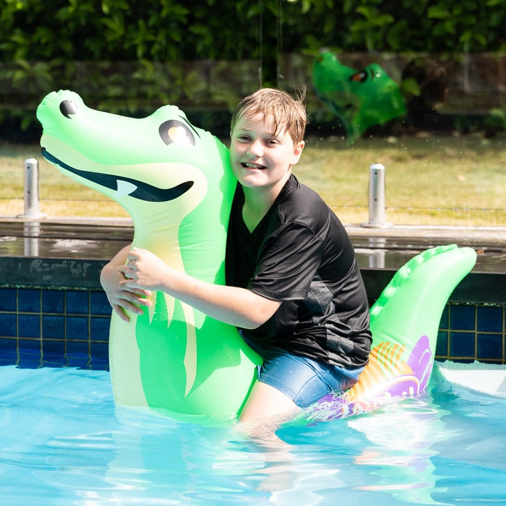 Child in pool on the Wahu Pool Pets Croc Racer