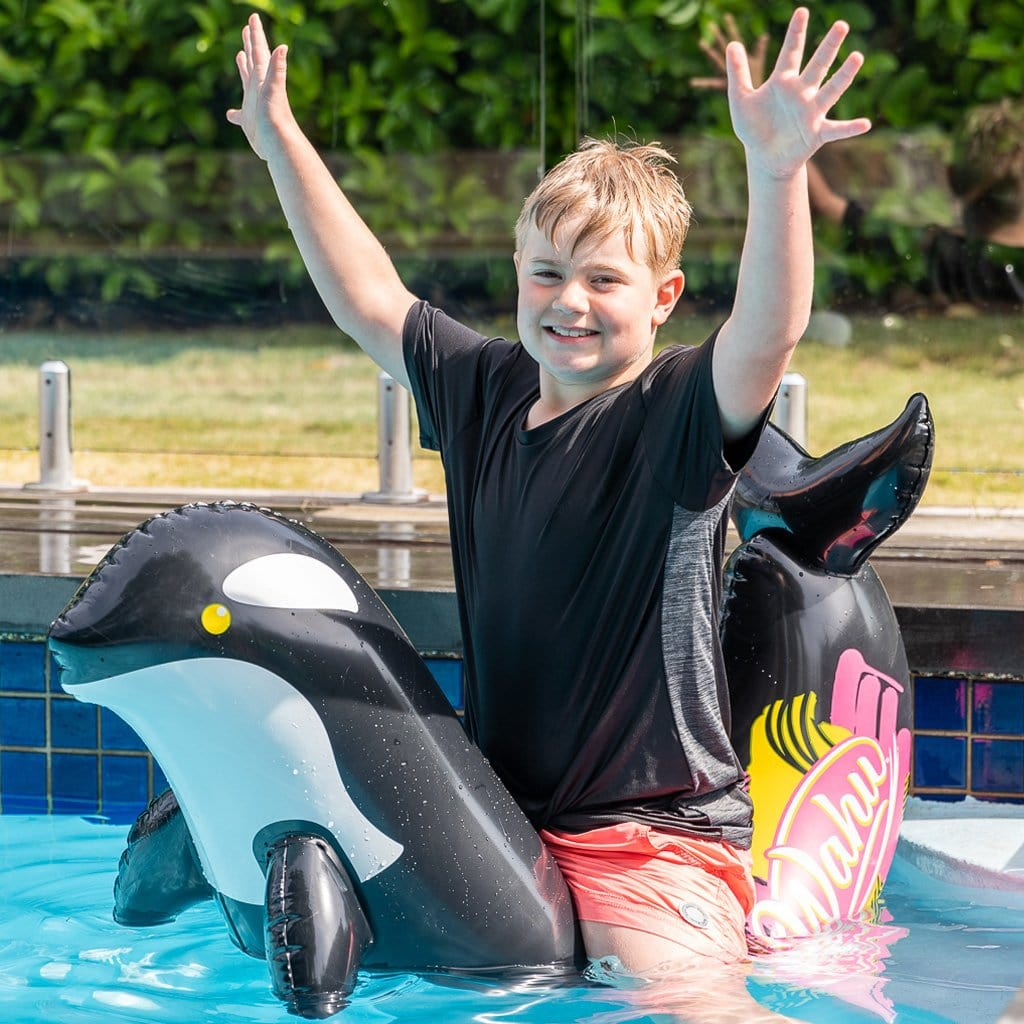 Child in pool on the Wahu Pool Pets Orca Racer