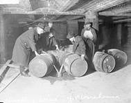 Agents destroying liquor barrels during 1920s prohibition.