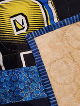 Load image into Gallery viewer, Turned up corner shows gold fabric backing and the binding around the quilt.