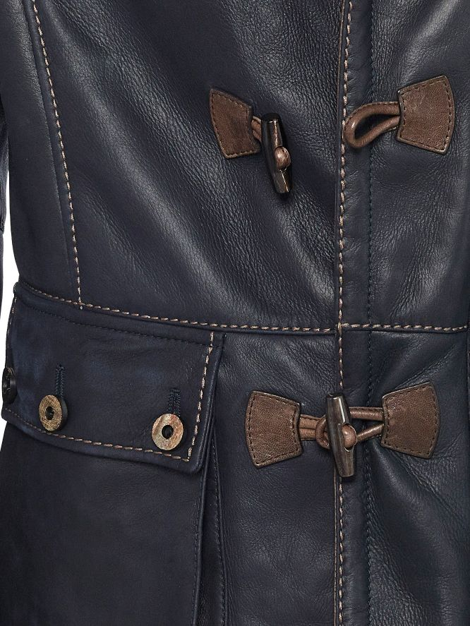 Water buffalo horn toggles and buttons secure the rich navy Spanish Astrakhan shearling