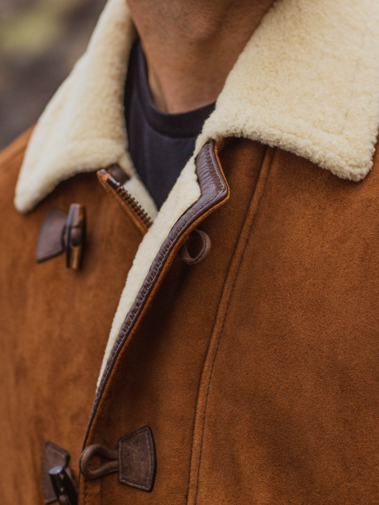 Dark brown lamb nappa secures toggle enclosures and reinforces the placket with perfect harmony on lamb suede