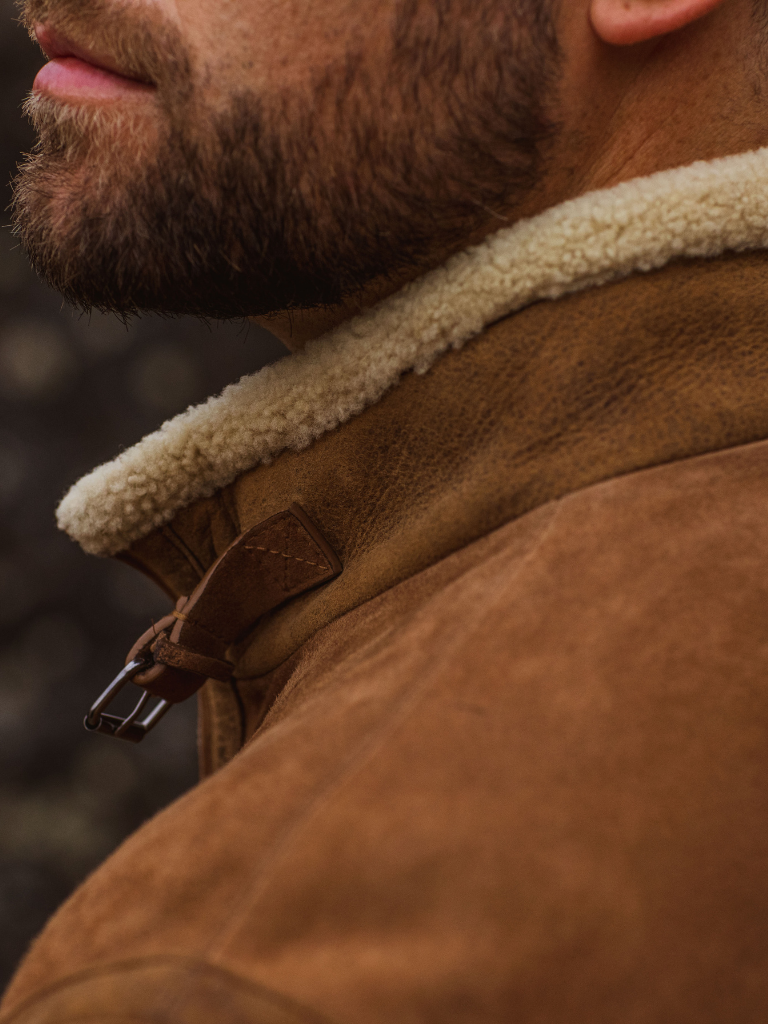 The caress of a baby lamb fleece collar is accentuated with a hand-burnished neck strap and antiqued metal buckle