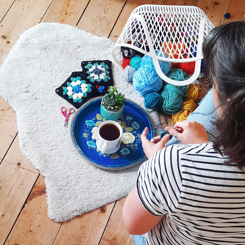 Pigeon is sat on the floor hooking crochet granny squares