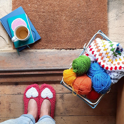 Feet wearing crochet slippers, stood on a doorstep with a basket of yarn and cup of tea
