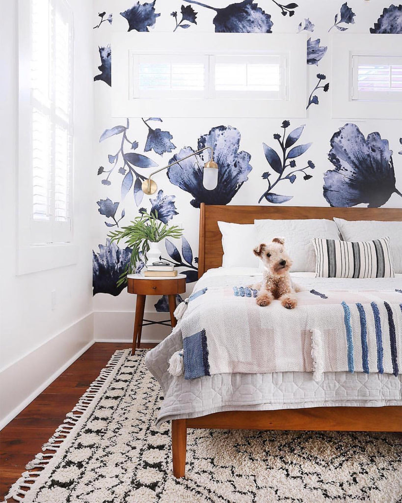 dog on a bed in front of floral wallpaper