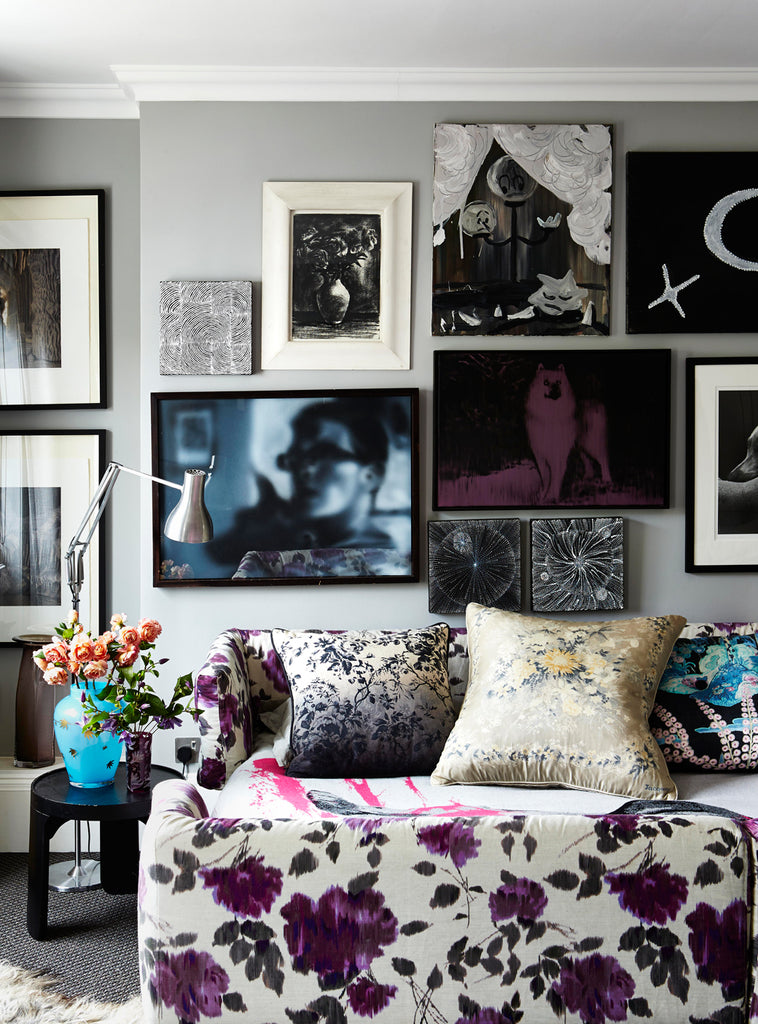 purple and white floral sofa with photo gallery wall