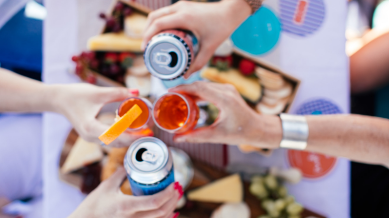 Hands holding cocktails and canned cannabis beverages