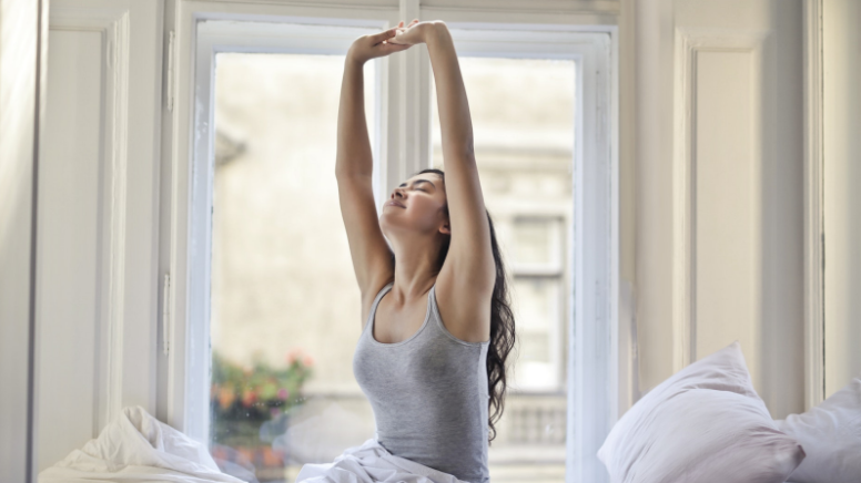 Woman stretching her arms after a good night's sleep