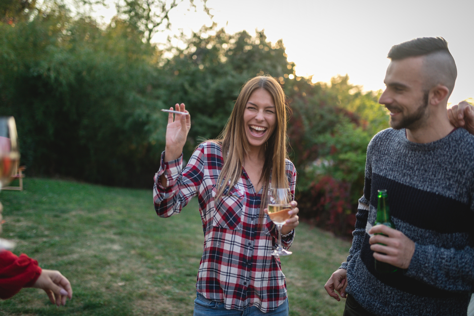 A woman laughing holding a joint at a party