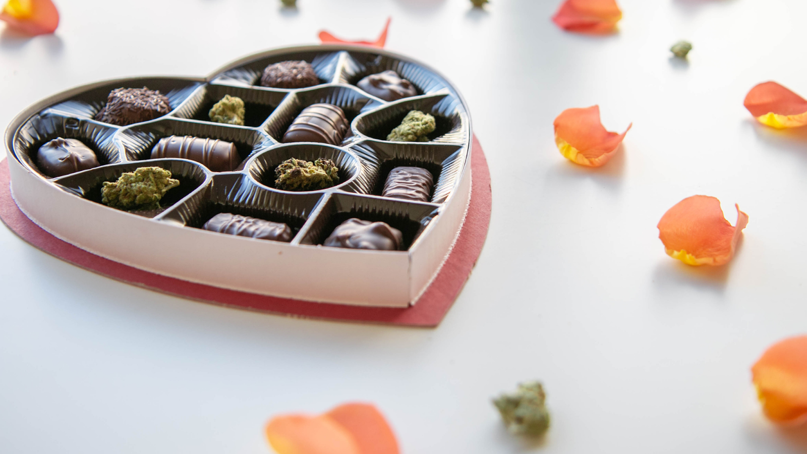 Chocolate edibles and cannabis buds in a heart-shaped box