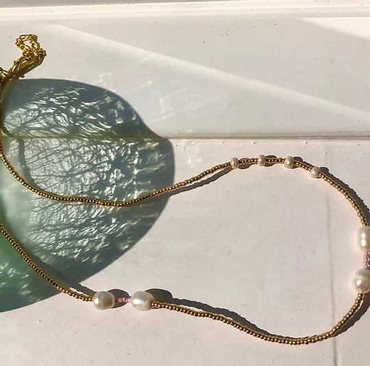 A gold beaded necklace with ethically-sourced fresh water pearls.