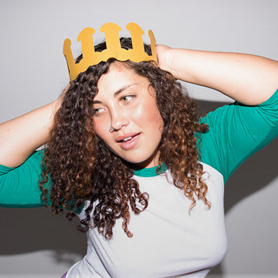 Girl wearing a dick crown and wearing a green and white shirt