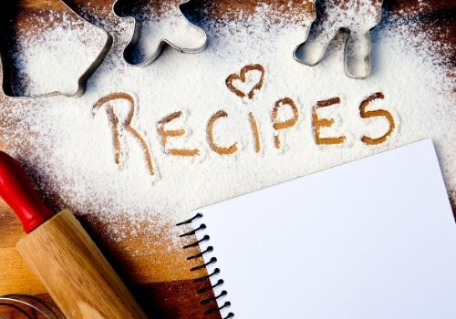 "Butcher block counter with icing sugar dusted thickly over a large surface with the word ""Recipes"" drawing by hand and a heart shape dotting the ""i"" in ""recipes"". There are metal cookie cutters strewn around & a rolling pin & notebook to the side."