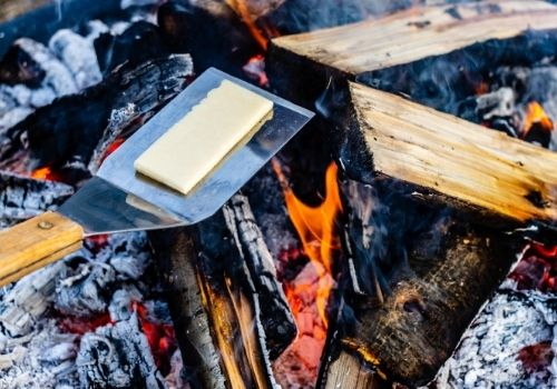 Over an open firepit fire with red coals and light flame, a metal BBQ spatula holds a thick slice of white aged cheddar as it begins to melt.