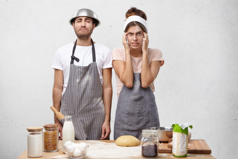 A man with a stainless steel baking bowl on his head and a woman holding her head in her hands are standing in the kitchen looking confused.